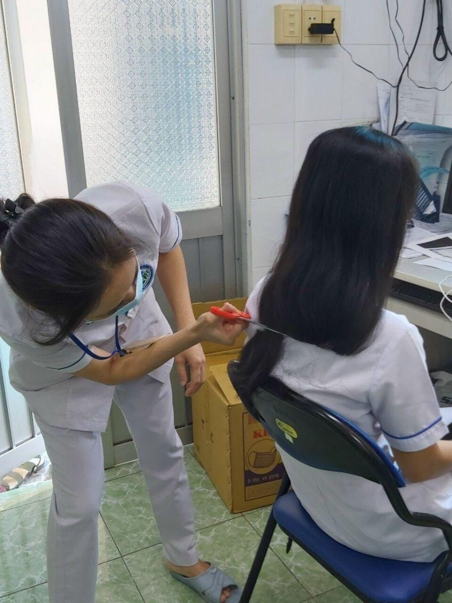 Nhờ đồng nghiệp cắt vội mái tóc để tiện cho công việc trong Trung tâm cách ly